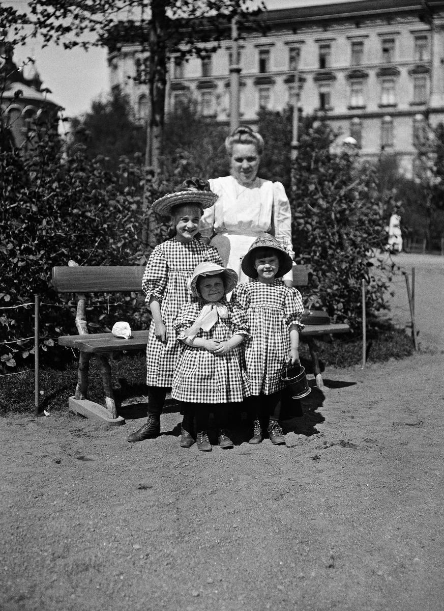 Lapsia Katajanokan puistossa lastenhoitajan tai kotiapulaisen seurassa 1910-luvulla, ks. myös kuva N1911.