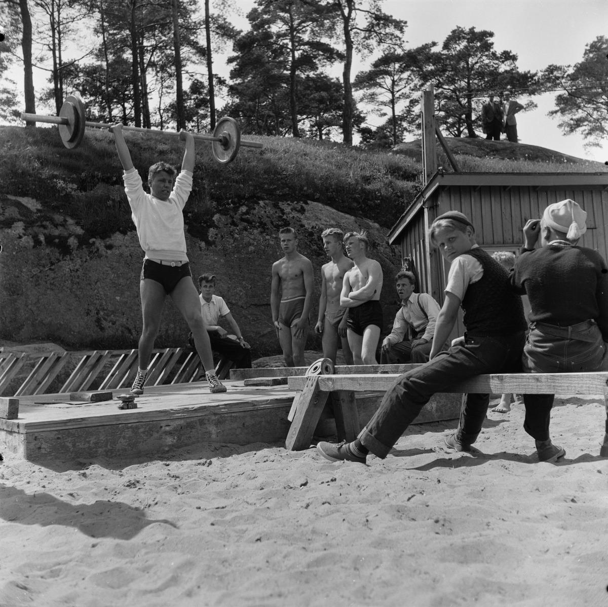 Miehet nostavat painoja Hietaniemen uimarannalla.