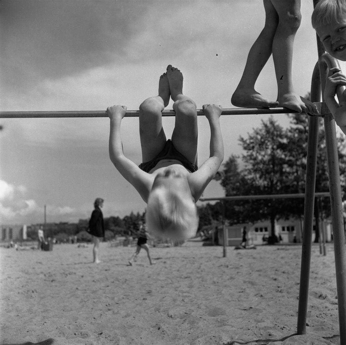 Pikkupojat leikkivät urheilutelineillä Hietaniemen uimarannalla.