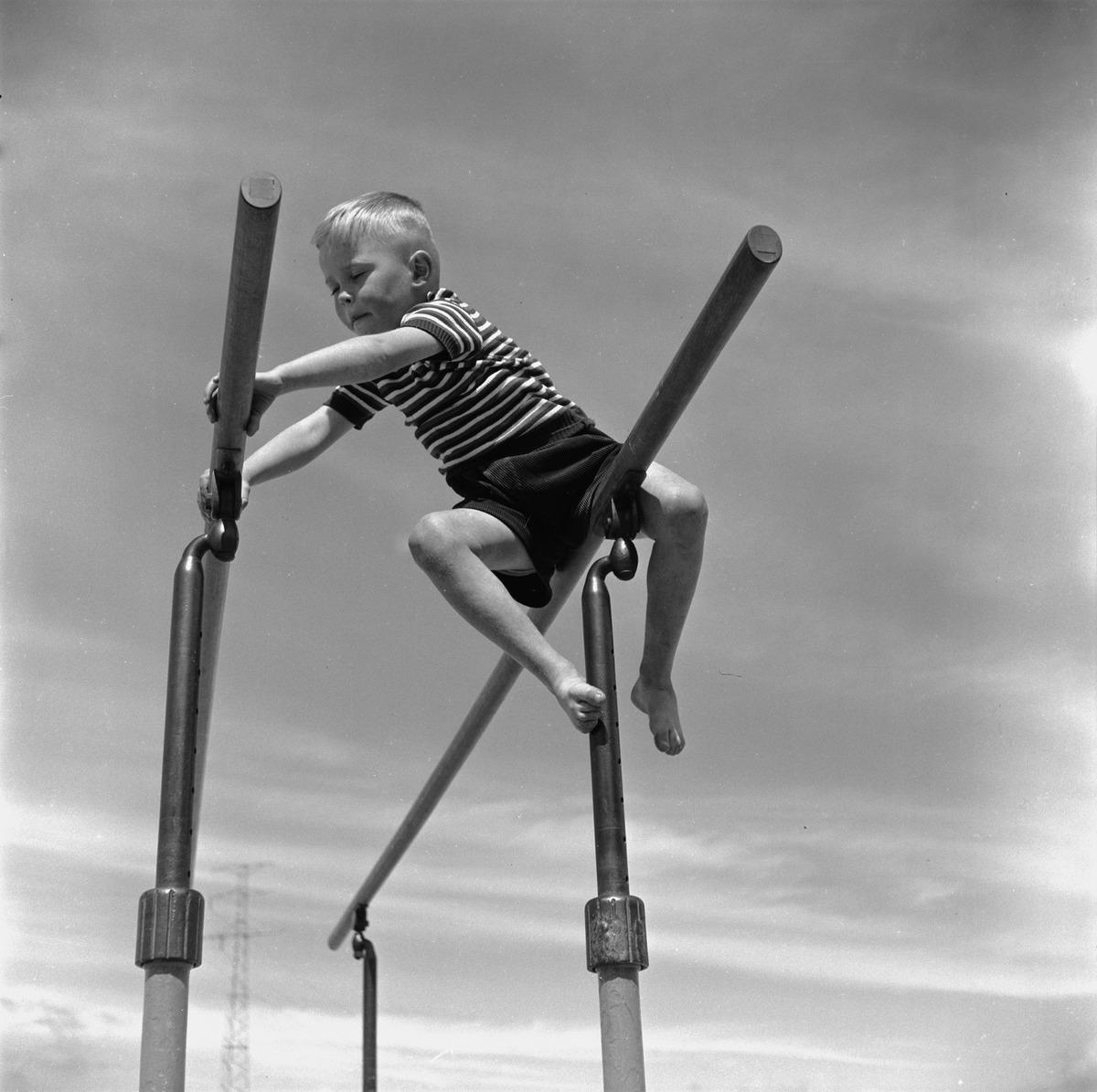 Pikkupoika leikkii nojapuilla Hietaniemen uimarannalla.