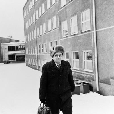 Suomen kielen opettaja seisoo Hykkylän koulun ja lukion (ent. Helsingin kaksoisyhteislyseo, nyk. Helsingin luonnontiedelukio) lumisella pihalla, Mäkelänkatu 93. Vuonna 1955 valmistuneessa rakennuksessa toimii nykyään Käpylän peruskoulu.