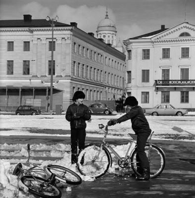 Kaksi poikaa polkupyörien kanssa Kauppatorilla.