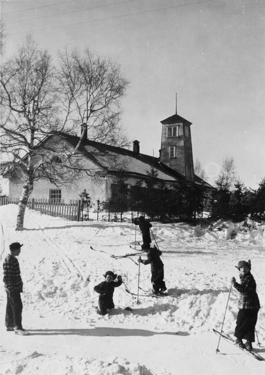Lapset laskemassa suksilla mäkeä Lauttasaaren palokunnan talon edustalla.