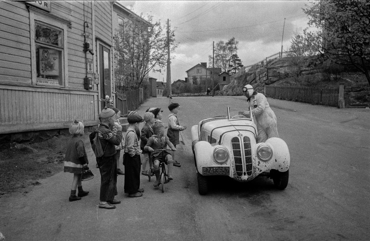 Pasila, Hertankatu 18, tontin alatalo, lapsia ihmettelemässä kauppias ja kilpa-ajaja Leo I. Mattilan BMW-merkkistä kilpa-autoa tämän kaupan edessä.