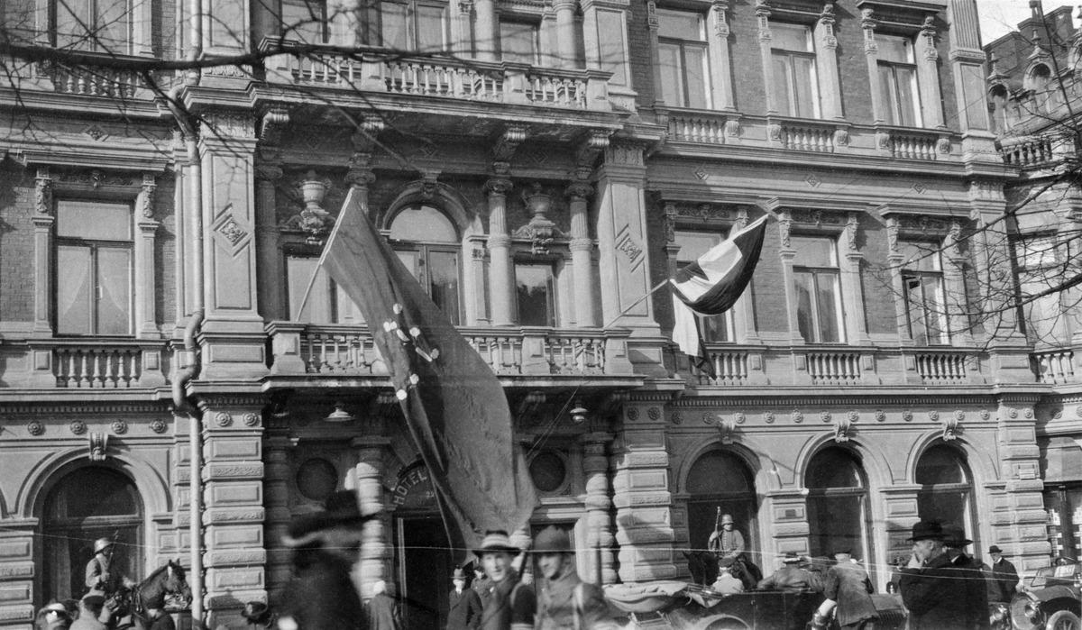 Helsingin valtaus 1918, saksalaisten esikunta hotelli Kämpissä, Pohjoisesplanadi 29. Vasemmalla punapohjainen Suomen lippu, oikealla vihreä-valko-musta Saksan valtakunnanlippu.