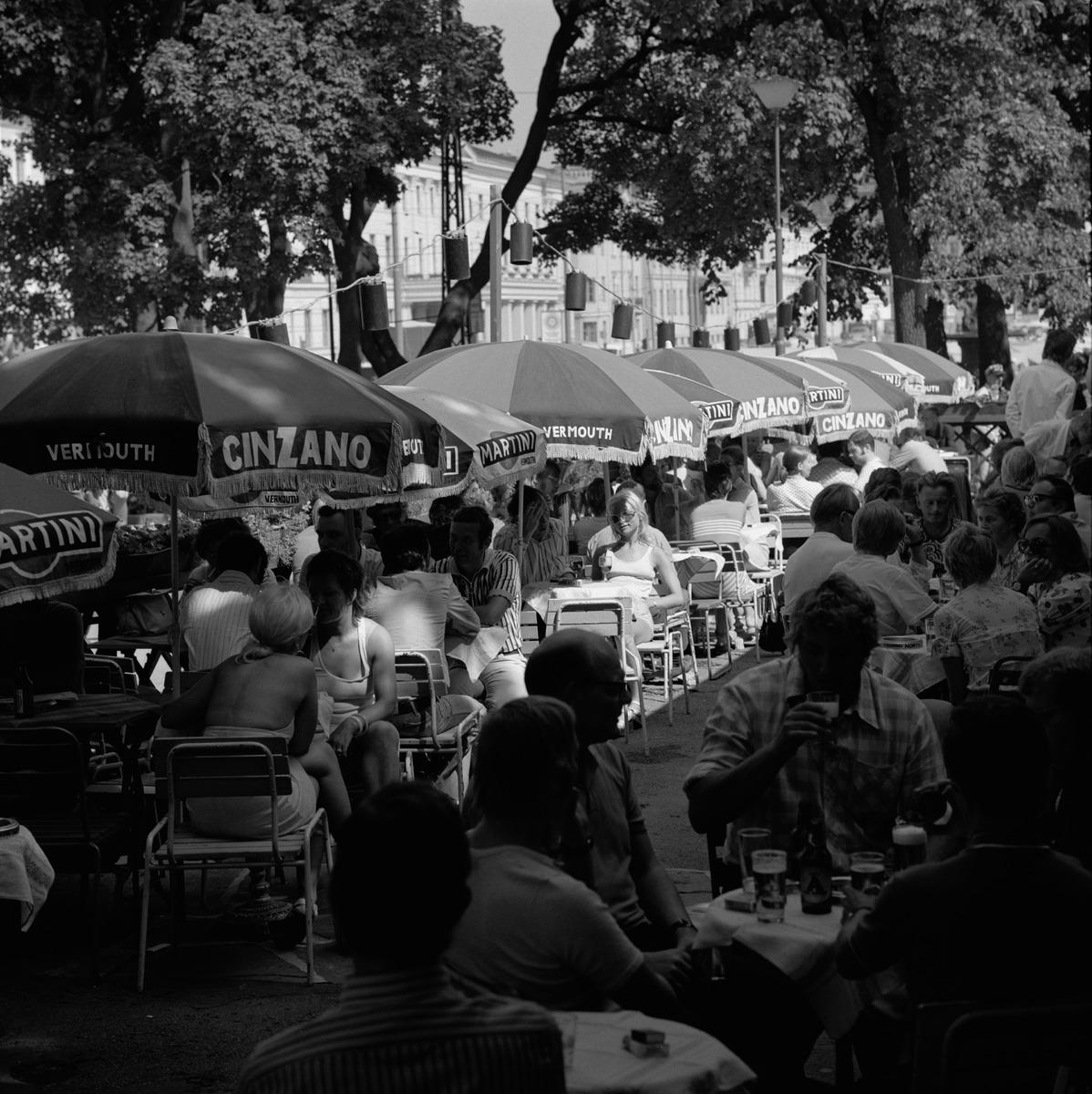 Ihmisiä ravintola Kappelin ulkoilmaterassilla Kappeliesplanadilla.