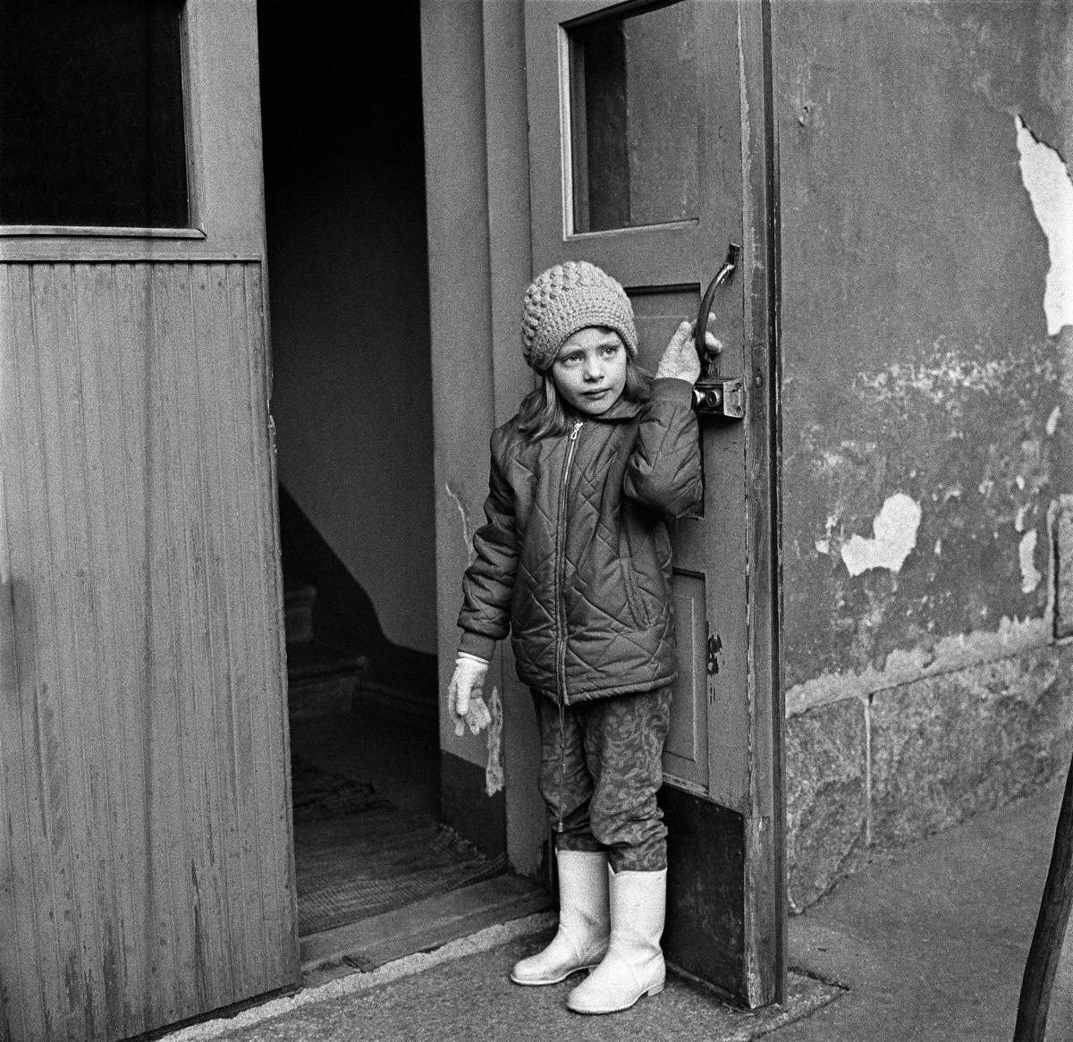 Tyttö seisoo kumisaappaissaan ulko-ovella