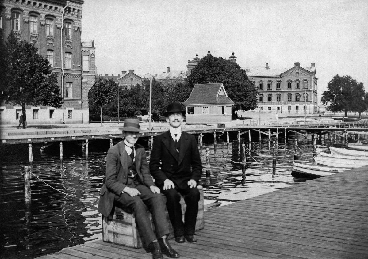 Kaksi miestä istuvat Pohjoisrannassa Halkolaiturilla