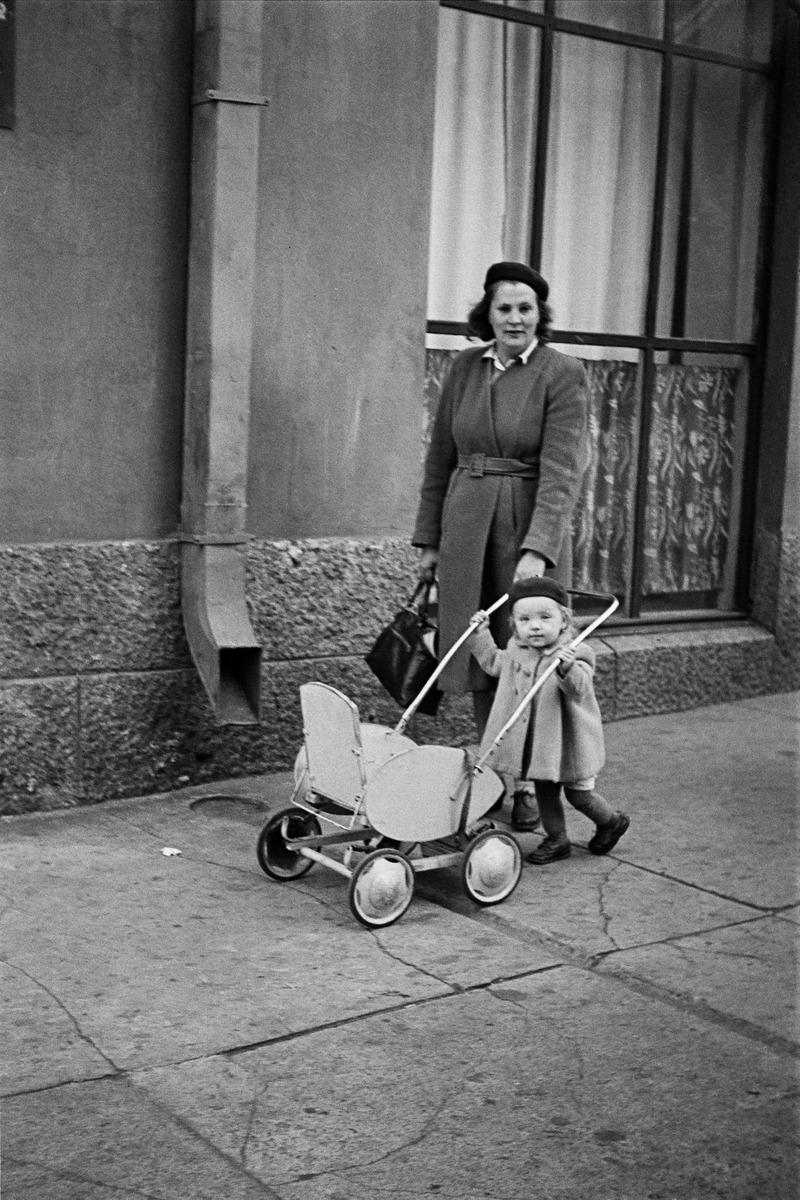 Torkkelinkatu 21:n edessä, nainen ja pieni tyttö, joka työntää lastenvaunuja.