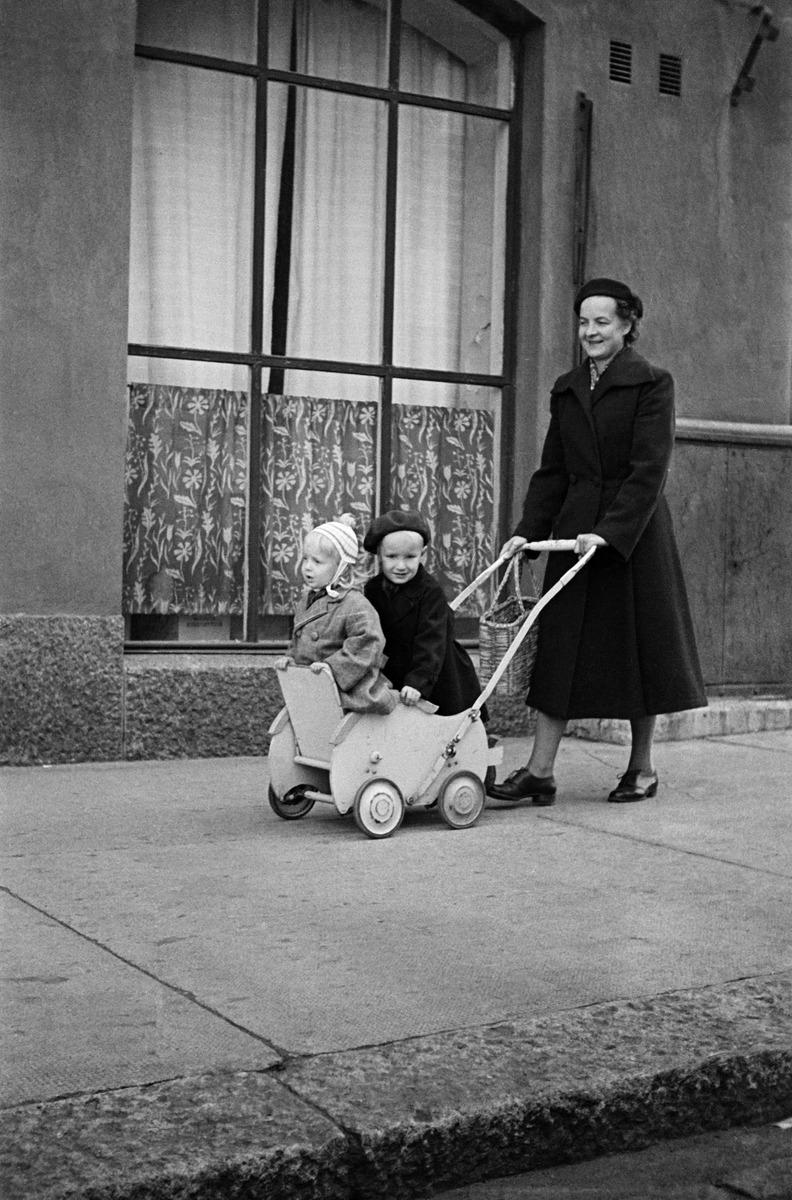 Torkkelinkatu 21:n edessä, nainen työntää lastenvaunuja, joissa kaksi lasta.