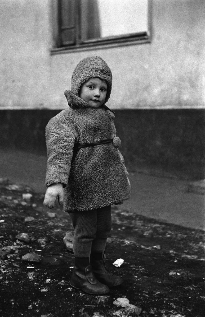 Pieni tyttö ulkona talon edessä.