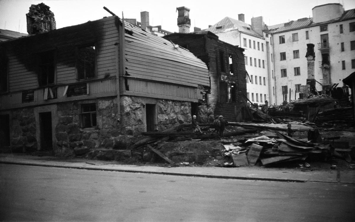 Tuhoutunut talo jossa palamisen jälkiä, vieressä seisoo pieniä poikia.