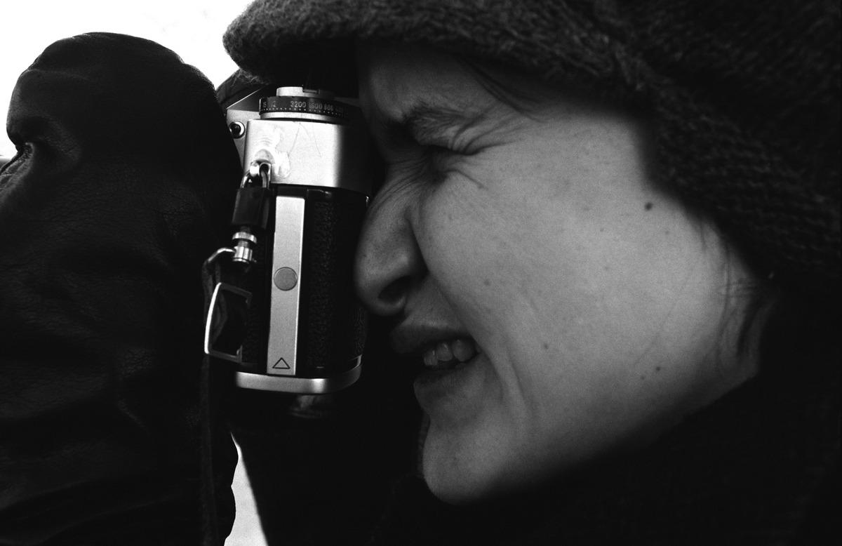 Valokuvauksenopiskelija Eeva Pakkala (nyk. Rista) valokuvaamassa rukkaset kädessä Leicaflex-kinofilmikameralla kylmänä pakkaspäivänä Kaivopuiston kallioilla.