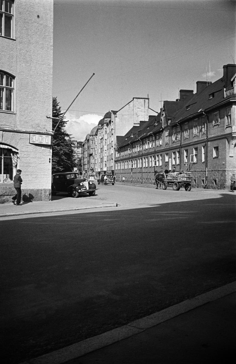 Näkymä Pietarinkadulta pohjoiseen pitkin Kapteeninkatua, oikealla Kapteeninkatu 7, 9. Vasemmalla talon seinässä Elannon kyltti, oikealla vaatturiliike sekä hevosen vetämät kärryt