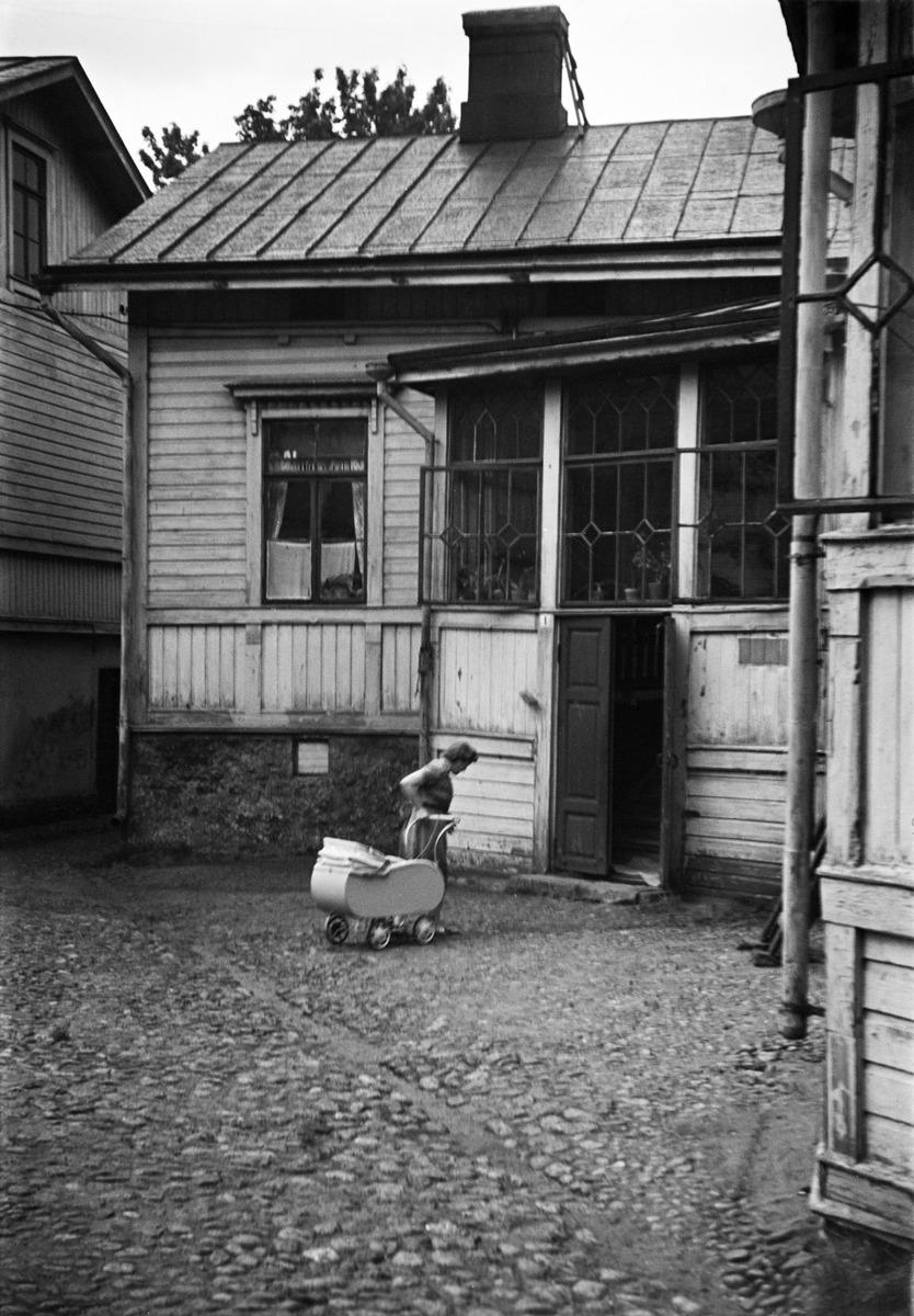 Lapinlahdenkatu 4:n sisäpiha, nainen työntää lastenvaunuja.