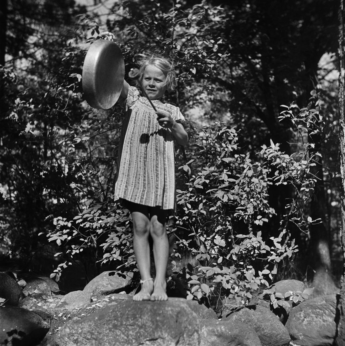 Tyttö seisoo kivellä ja ilmoittaa ruoka-ajasta lyöden gongia (kattilan pohjaa)