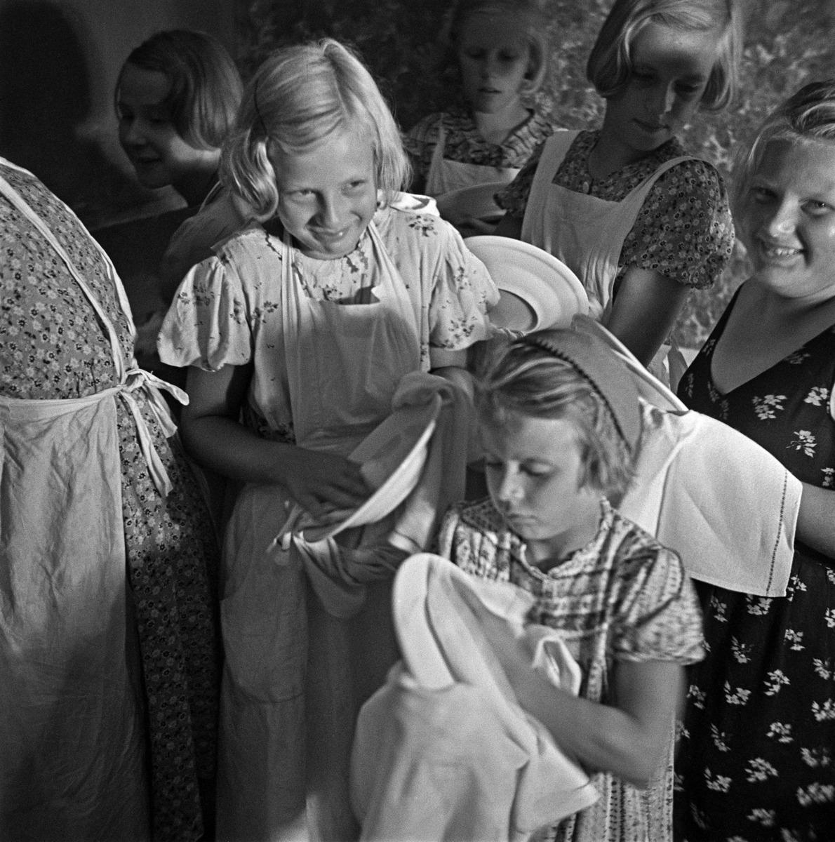 Tytöt kuivaavat astioita