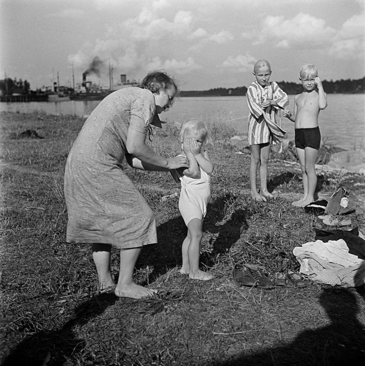 Lapsia uinnin jälkeen rannalla, pienintä puetaan