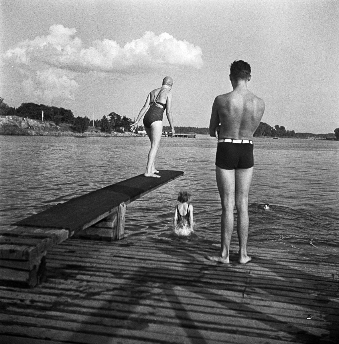 Tyttö valmistautuu sukeltamaan ponnahduslaudalta, mies katsoo rannalta