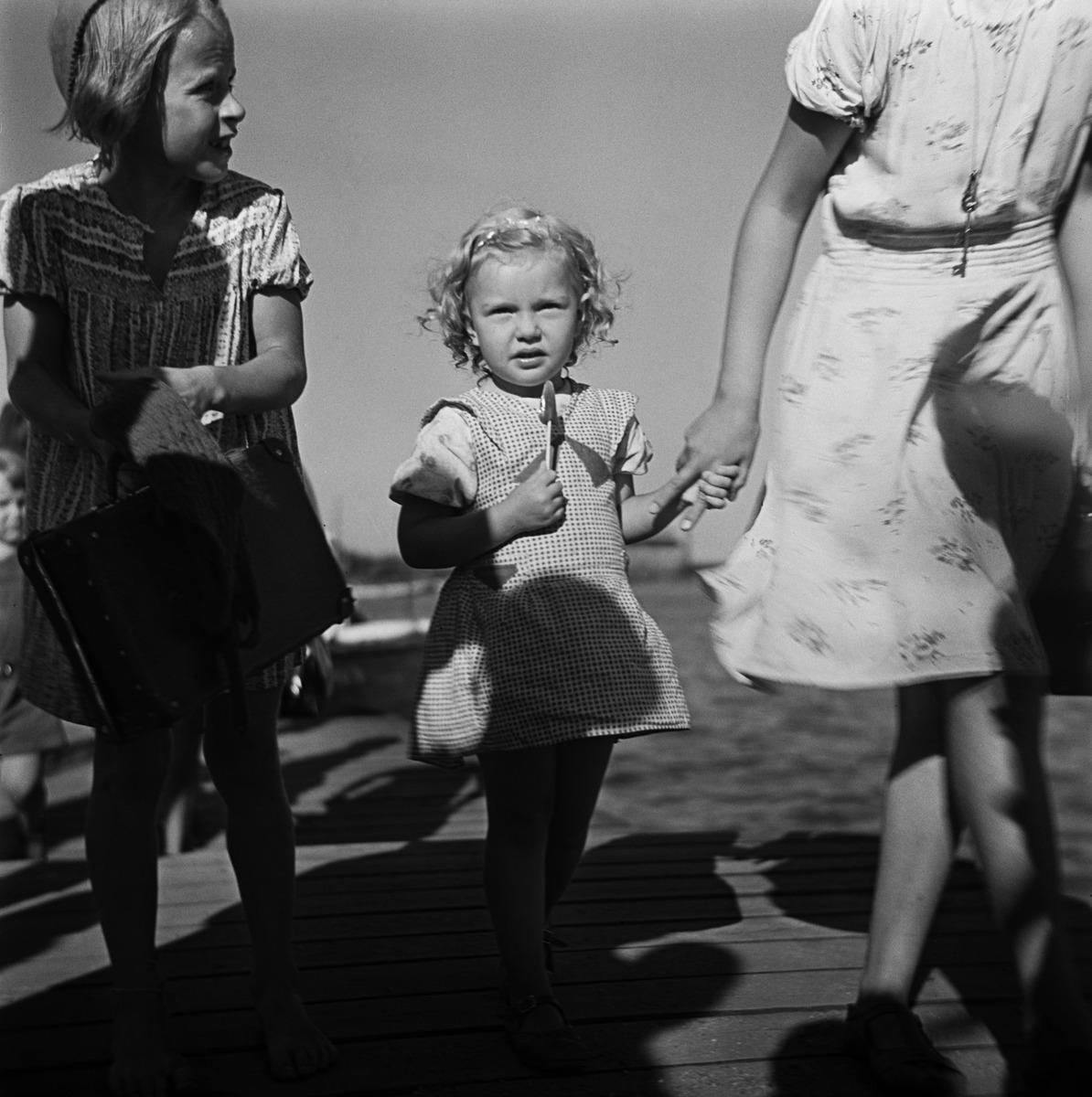 Kaksi pikkutyttöa isomman tytön kanssa laiturilla