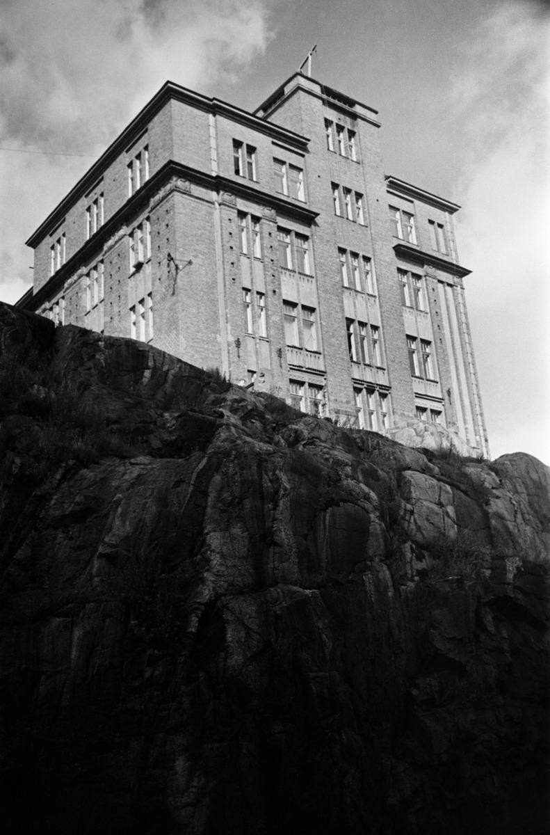 Siltavuorenpenger 20D Oikokadulta nähtynä, rakennus jyhkeiden kallioiden päällä