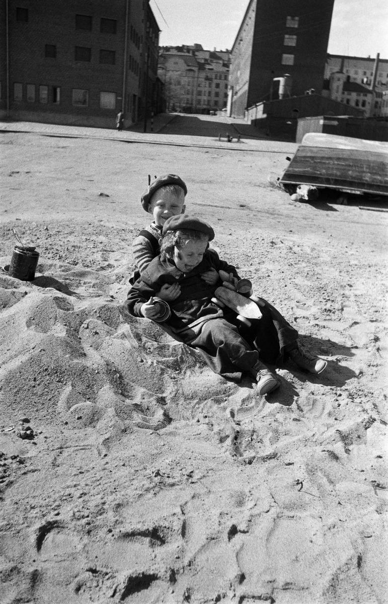 Lapset leikkimässä hiekkakasalla Sörnäisten rantatiellä