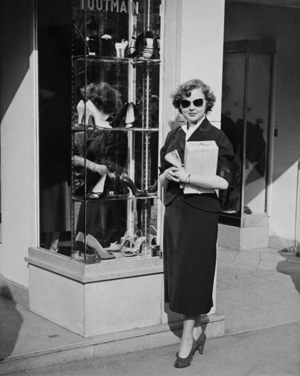 Nainen poseeraa Pariisissa kenkäkaupan edustalla aurinkolasit päässä