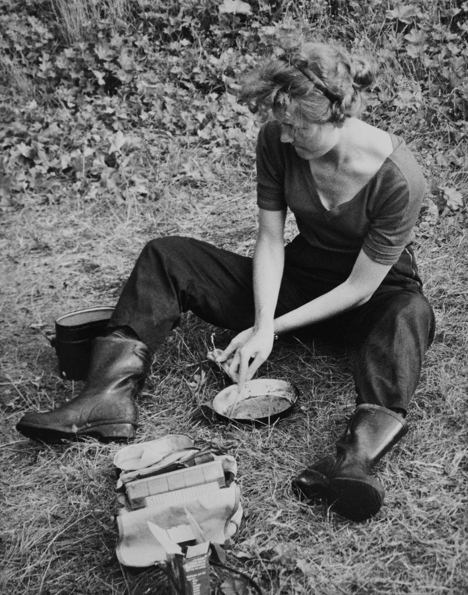 Nainen pesee paistinpannua nurmikolla matkalla Norjan Lapissa.