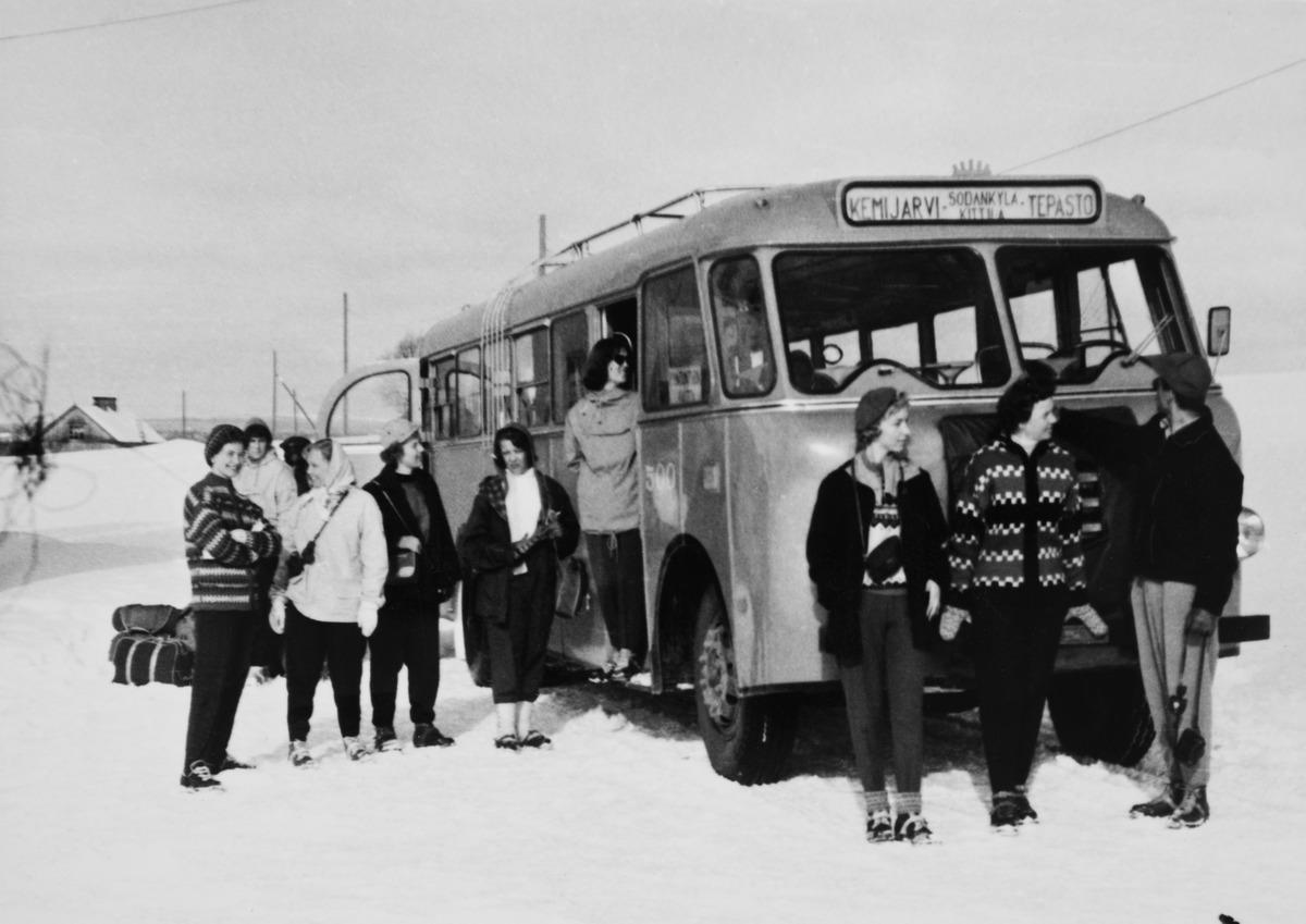 Hiihtoasuinen helsinkiläisseurue astumassa Kemijärvelle menevään linja-autoon