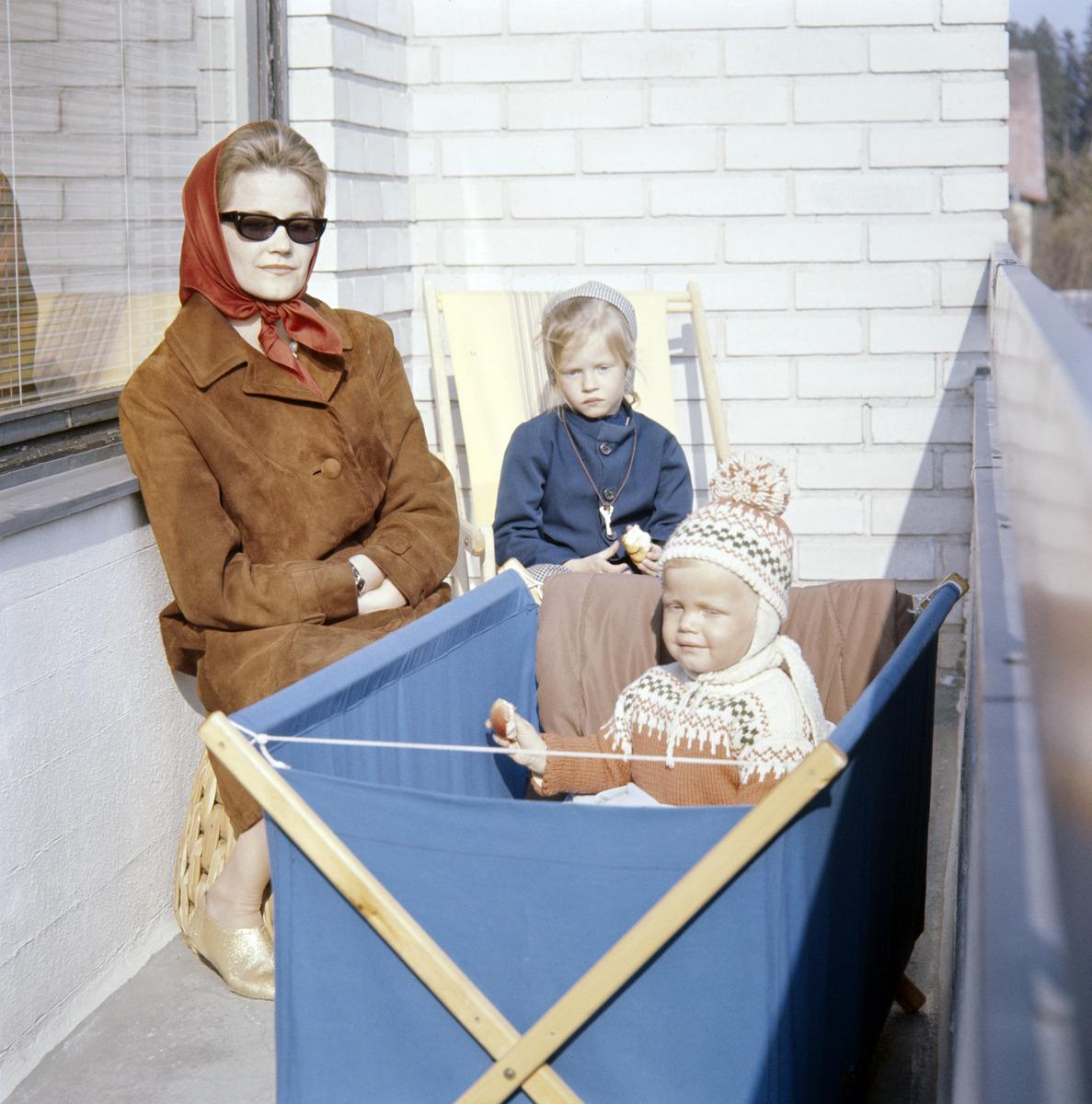 Äiti lasten kanssa parvekkeella aurinkolasit päässä