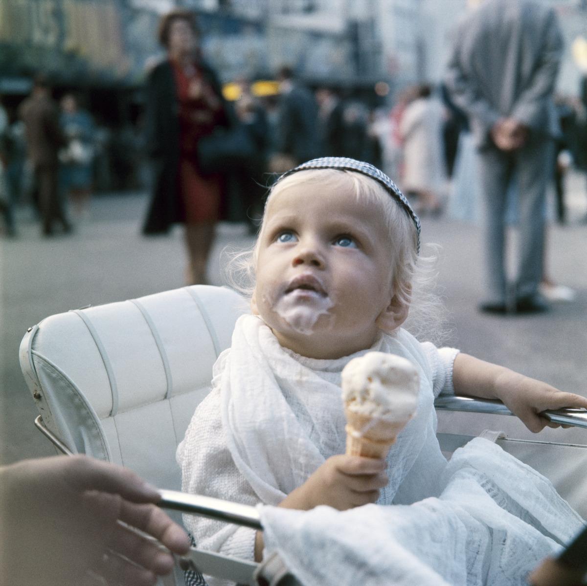 Pikkupoika syö jäätelöä lastenvaunuissa Linnanmäellä.