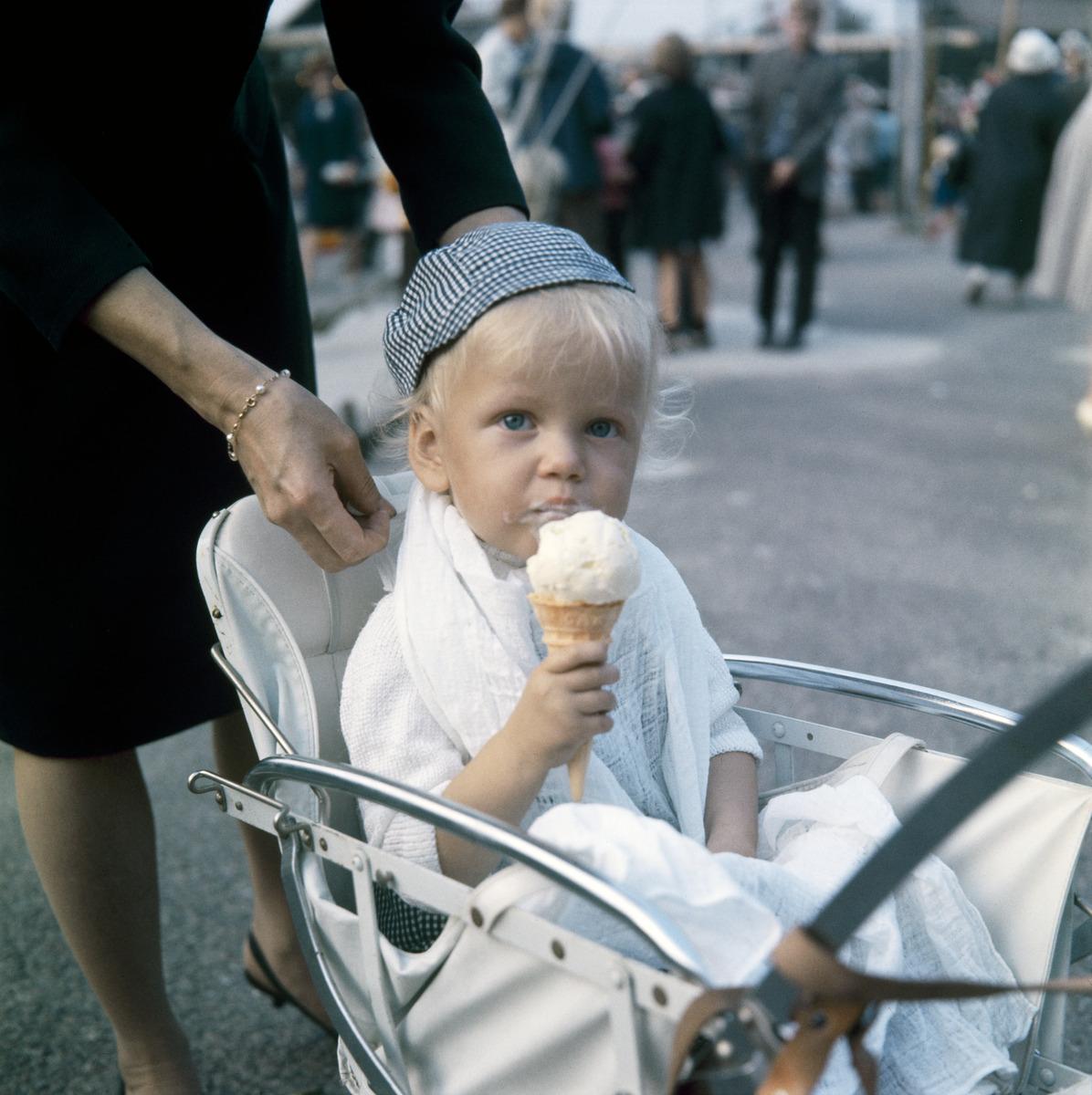 Pikkupoika syö jäätelöä lastenvaunuissa pieni lippalakki päässä, tötterö kädessä Linnanmäellä.