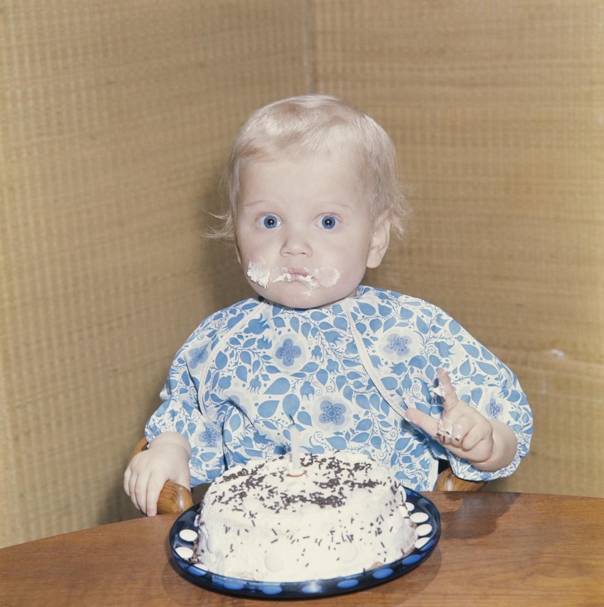 Pikkupoika maistelee syntymäpäiväkakkua