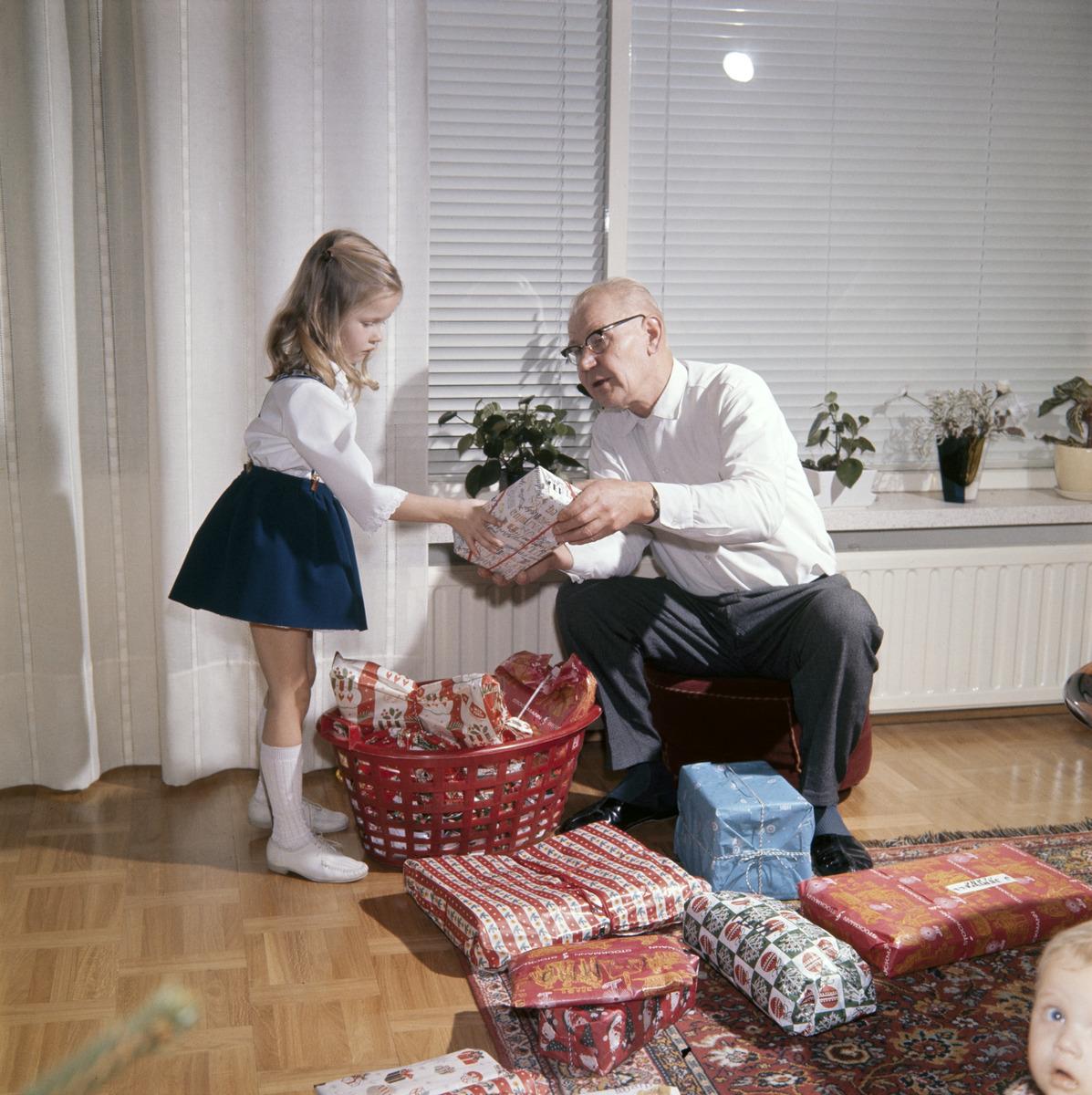 Isoisä ojentaa lahjaa tytölle jouluaattona.