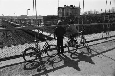 Kaksi poikaa (Tuomas Heikkilä ja Aapo Rista) polkupyörineen katselemassa junien kulkua Linnunlaulun sillalla