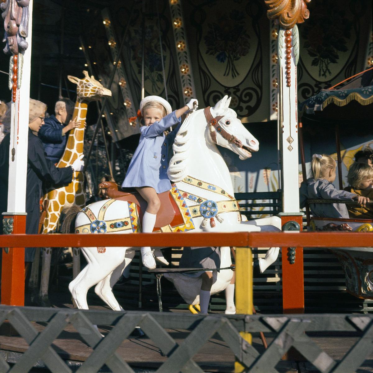 Lapsi ratsastaa leikkihevosen selässä karusellissa Linnanmäellä.