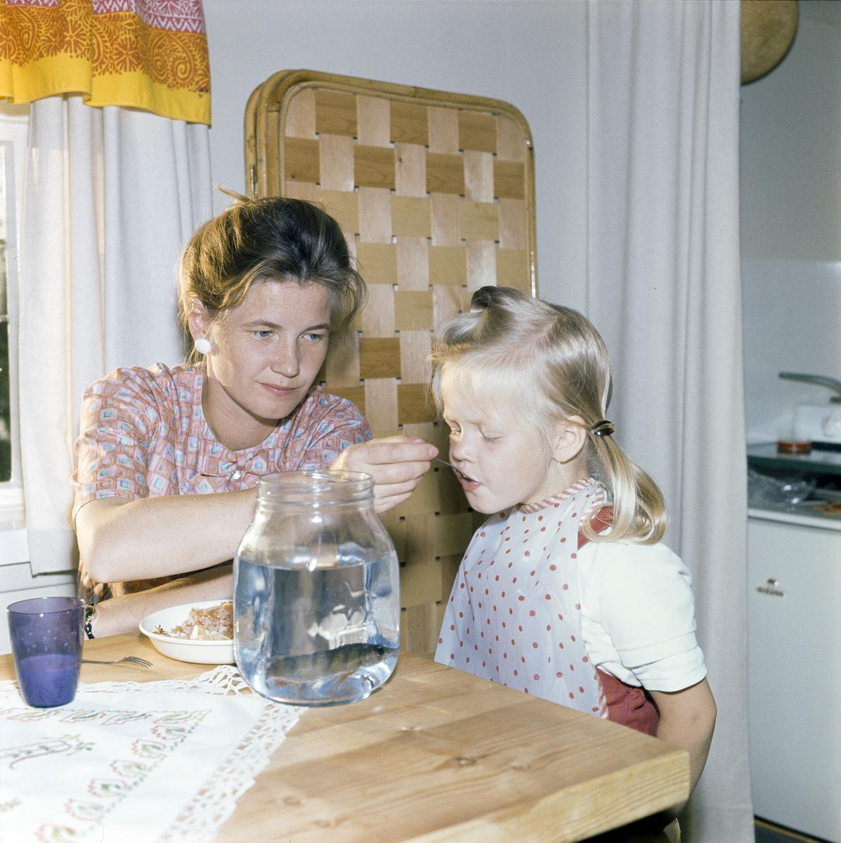 Nainen syöttää pientä lasta keittiön pöydän ääressä
