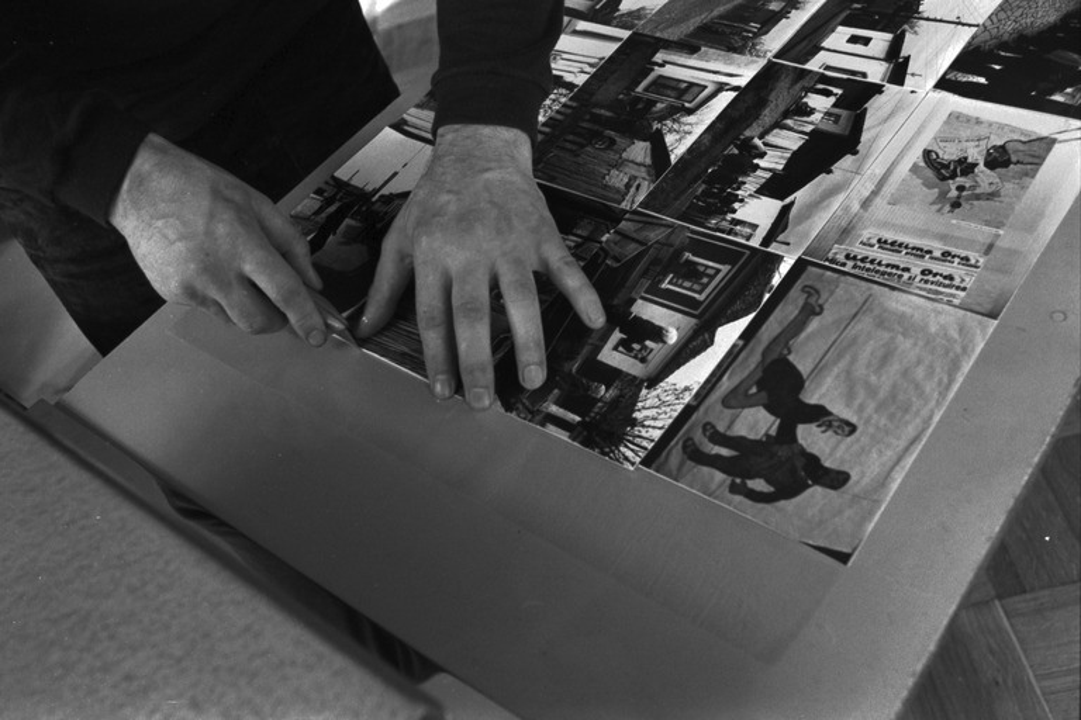 Liisankatu 7. Valokuvaaja Simo Rista leikkaamassa Stanley-veitsellä erilleen Romania-aiheisen valokuvakirjan kuumaliimapuristimella liimattuja kuvia.