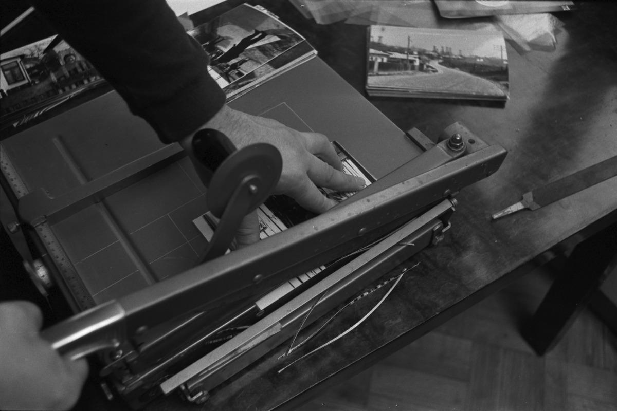 Liisankatu 7. Valokuvaaja Simo Rista leikkaamassa leikkurilla Romania-aiheisen valokuvakirjan kuvia.