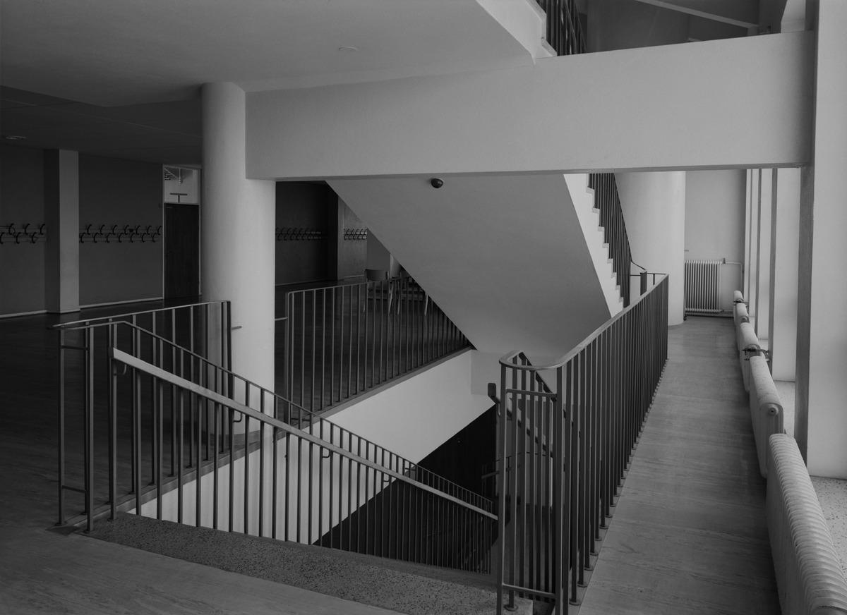 Näkymä kerroksen aulatilan portaikosta Etu-Töölössä sijaitsevassa Taivallahden kansakoulussa (nyk. Taivallahden peruskoulu), Eteläinen Hesperiankatu 38. Kuvassa näkymä avautuu alaspäin meneviin portaisiin