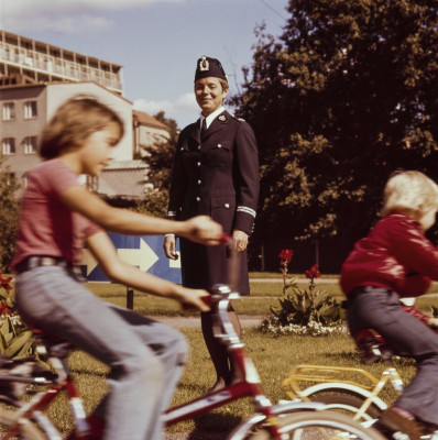 Lapset pyöräilevät Lasten liikennekaupungissa, poliisi hymyilee.