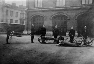Sairaankuljetuskalustoa miehistöineen Pääpaloaseman pihalla v. 1907 Vas. kannettavat paarit, keskellä työntöpaarit ja oik. polkupyöräpaarit
