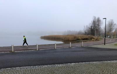 Ulkoiluasuun pukeutunut lenkkeilijä kävelee kuulokkeet korvillaan Töölönlahden rannalla Töölönlahden puistossa