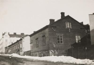 Kaksi matalaa puutaloa, Eerikinkatu 48. Kuvan vasemmassa laidassa Hietalahdenkadun toisella puolella näkyvän kivitalon Eerikinkatu 46 suunnitteli rakennusmestari Emil Lindgren 1901.