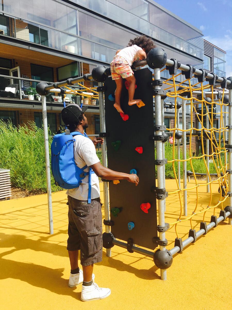 Leikkipuisto, pieni tyttö kiipeilemässä kiipeilytelineessä