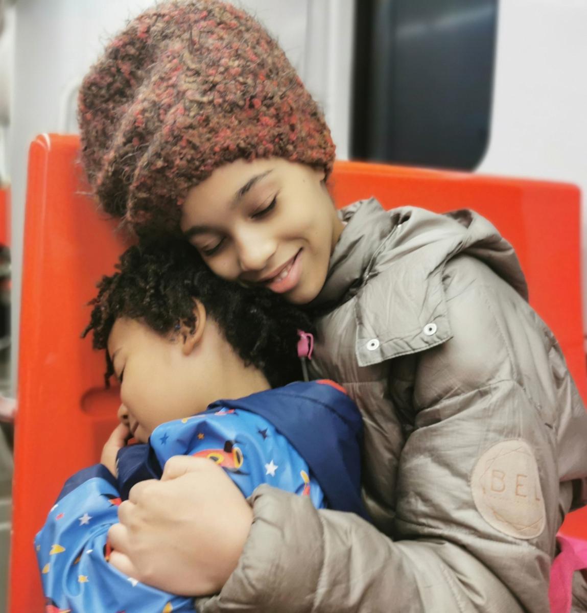 Sisarukset metrossa Helsingissä, kuvassa sisko halaa veljeä.