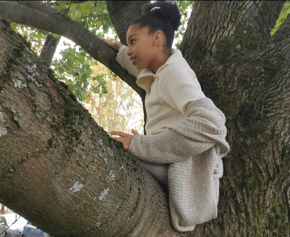 Puussa kiipeilyä, kuvassa tyttö istuu puunoksalla.