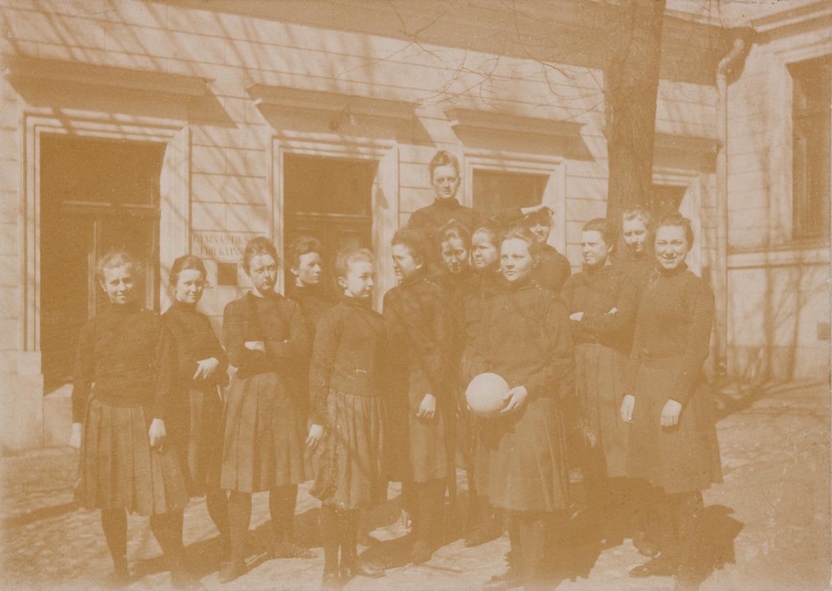 Voimistelunopettajaksi opiskelevat nuoret naiset yhtenäisissä asuissaan seisovat Helsingin yliopiston voimistelulaitoksen, Gymnastikskola för kvinnor, edessä