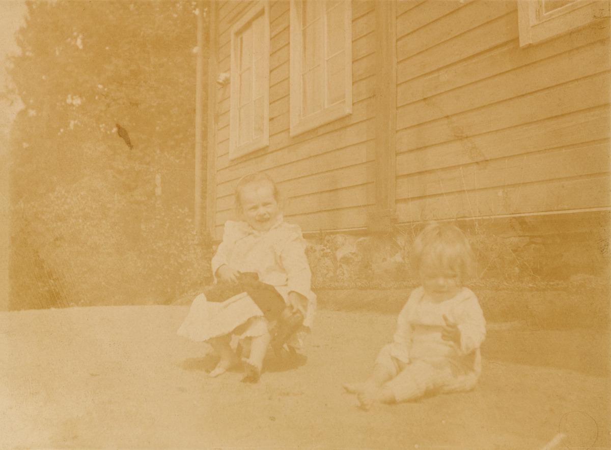Majgret ja Majbritt istuvat pihalla leikkimässä, isompi jakkaralla ja pienempi hiekalla