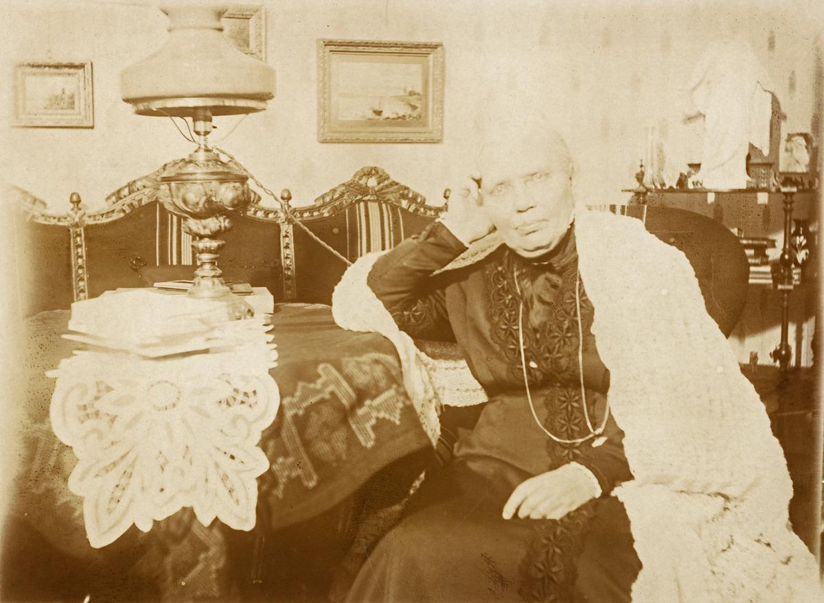 Anna Blomqvist (1840 - 1925) istuu pöydän ääressä kotonaan, Albertinkatu 23. Laulaja, laulupedagogi ja saksan kielen opettaja tunnettiin aktiivisena naisten aseman ja koulutuksen edistäjänä.
